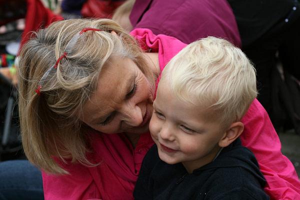Mutter haelt Kleinkind vor sich im Arm und fluestert etwas ins Ohr.