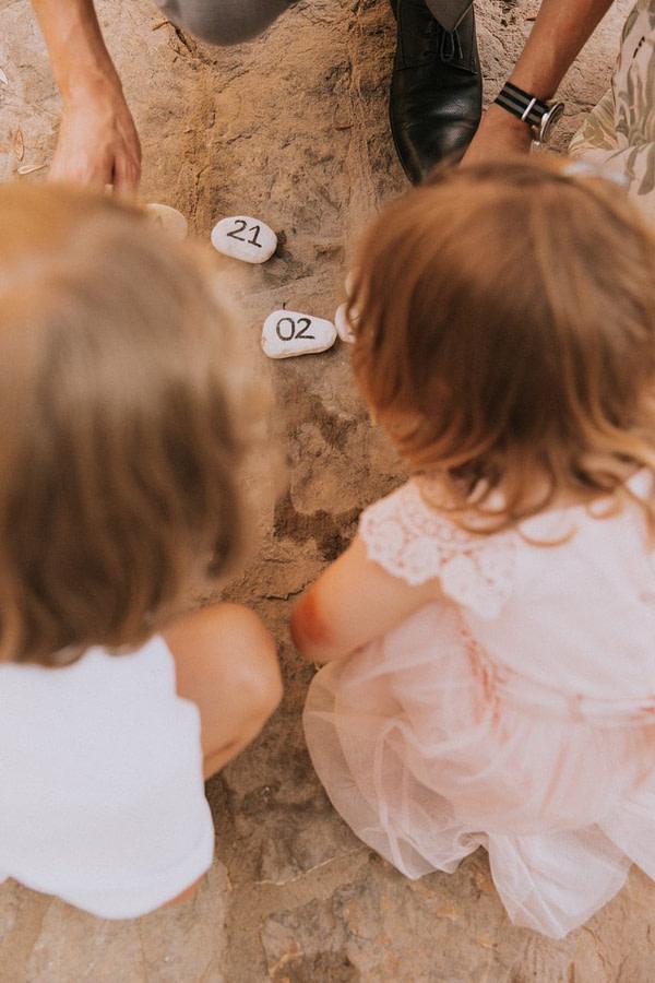 Zwei Kinder von hinten spielen hockend am Boden ein Spiel.